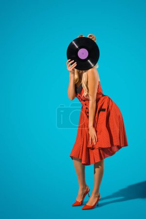 obscured view of woman in vintage dress covering head with vinyl record on blue background