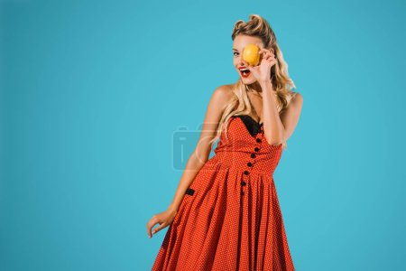 portrait of stylish pin up woman in vintage dress with fresh lemon isolated on blue