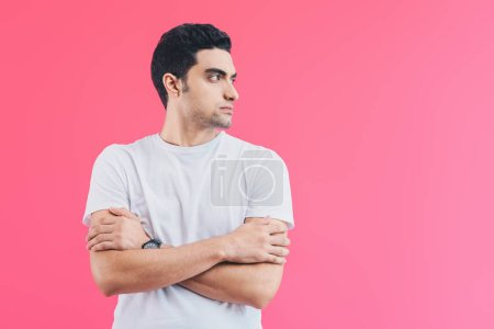 handsome man standing with crossed arms and looking away isolated on pink