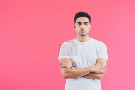 Photo for Serious handsome man standing with crossed arms and looking at camera isolated on pink - Royalty Free Image