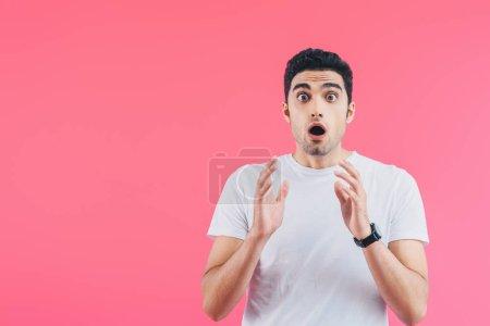 impactado hombre guapo gesto y mirando a la cámara aislado en rosa