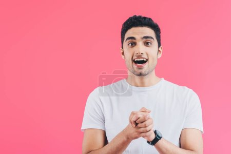 Photo for Excited handsome man holding hands together and looking away isolated on pink - Royalty Free Image