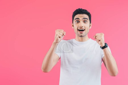 surprised happy handsome man cheering and showing yes gesture isolated on pink
