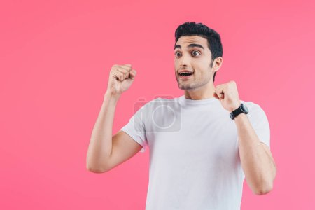 shocked handsome man showing yes gesture isolated on pink