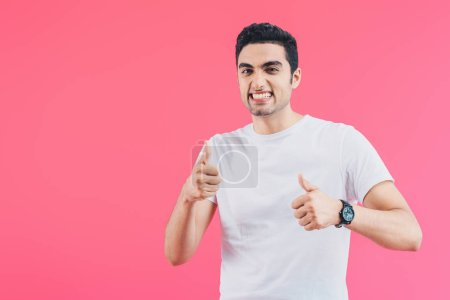 Photo for Grimacing smiling man showing thumbs up isolated on pink - Royalty Free Image