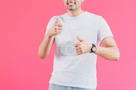 cropped image of smiling man showing thumbs up isolated on pink