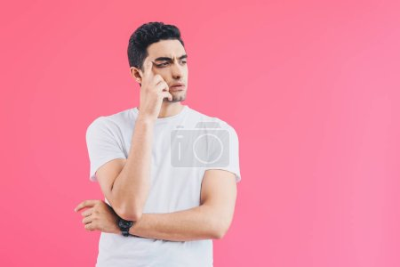 pensive handsome man touching head and looking away isolated on pink