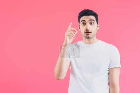 surprised handsome man showing idea gesture isolated on pink