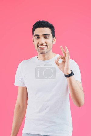 happy handsome man showing okay gesture isolated on pink