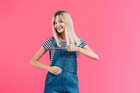 happy beautiful girl in denim overall showing thumb up and looking at camera isolated on pink