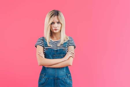 irritated girl in denim overall standing with crossed arms and looking at camera isolated on pink