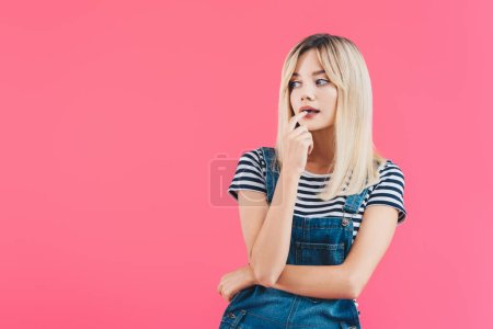 pensive beautiful girl in denim overall touching lips and looking away isolated on pink