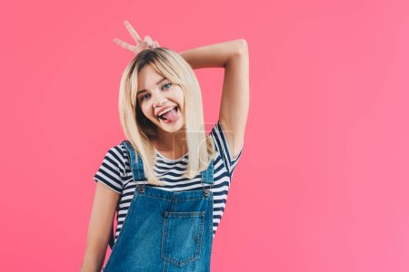 smiling beautiful girl in denim overall sticking tongue out and showing bunny ears isolated on pink