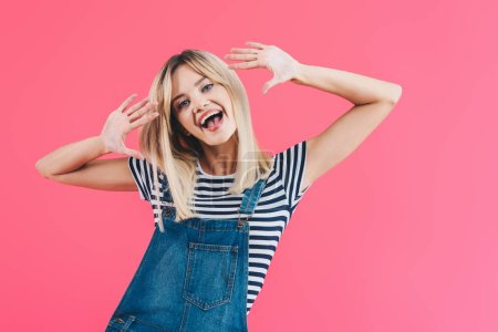 smiling beautiful girl in denim overall sticking tongue out, gesturing and looking at camera isolated on pink