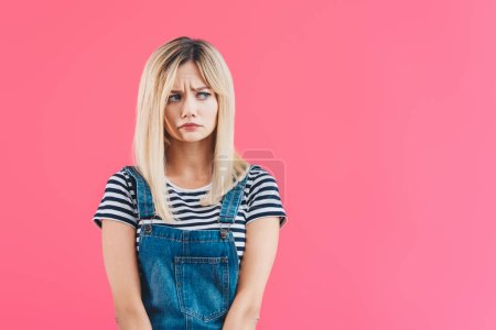 Photo for Worried beautiful girl in denim overall looking away isolated on pink - Royalty Free Image