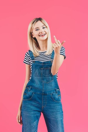 Photo for Smiling beautiful girl in denim overall showing middle finger isolated on pink - Royalty Free Image
