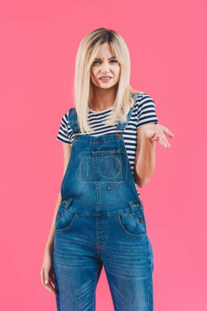 grimacing girl in denim overall gesturing and looking at camera isolated on pink