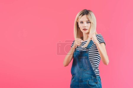 beautiful girl standing in fighting position with fists in denim overall isolated on pink