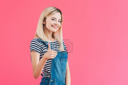 smiling beautiful girl in denim overall showing thumb up isolated on pink