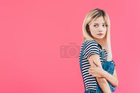 sad girl in denim overall hugging herself and looking away isolated on pink