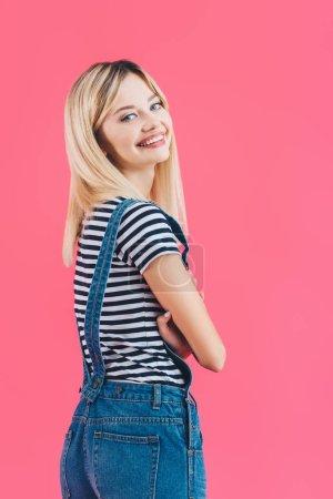 Photo pour Souriant de belle fille en denim globalement debout avec les bras croisés et regarder la caméra isolée sur rose - image libre de droit