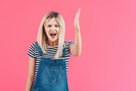angry girl in denim overall yelling and gesturing isolated on pink