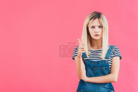 irritated girl in denim overall pointing on something isolated on pink