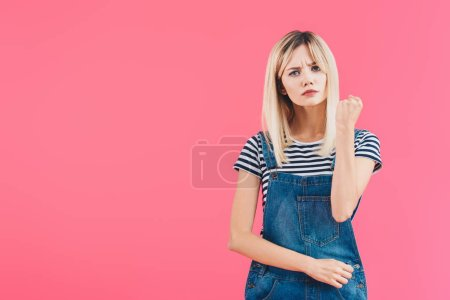 angry girl in denim overall showing fist isolated on pink