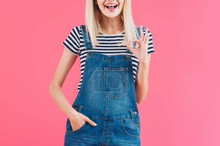 Photo for Cropped image of smiling girl in denim overall showing okay gesture isolated on pink - Royalty Free Image