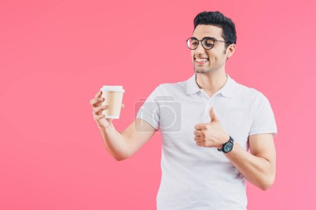 happy handsome man looking at coffee in paper cup and showing thumb up isolated on pink
