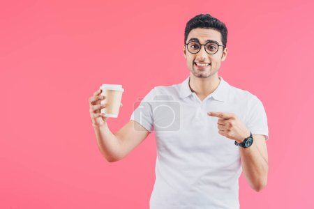 Photo for Happy handsome man pointing on disposable coffee cup isolated on pink - Royalty Free Image