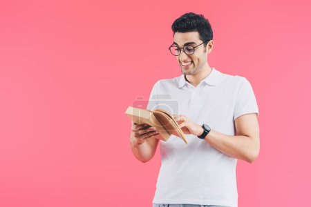 grimacing smiling student reading book isolated on pink