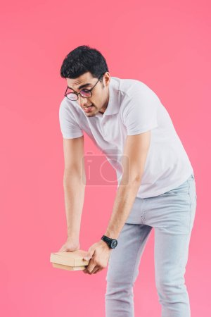 handsome grimacing student holding heavy books isolated on pink