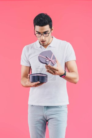 shocked handsome man looking into gift box in shape of heart isolated on pink, st valentine concept
