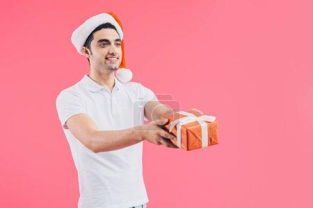 Foto de Sonriente hombre guapo santa sombrero dando caja de regalo aislado en color de rosa, concepto de año nuevo - Imagen libre de derechos