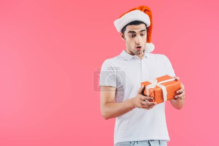 shocked handsome man in santa hat looking at gift box isolated on pink, new year concept