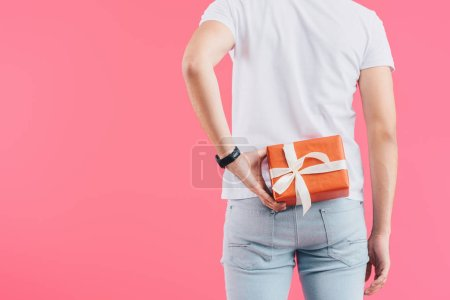 cropped image of man holding gift box behind back isolated on pink