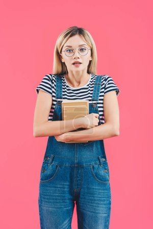 scared student in striped shirt and denim overall holding books and looking at camera isolated on pink
