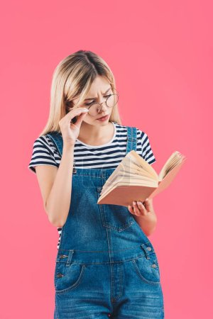portrait of young woman in eyeglasses reading book isolated on pink