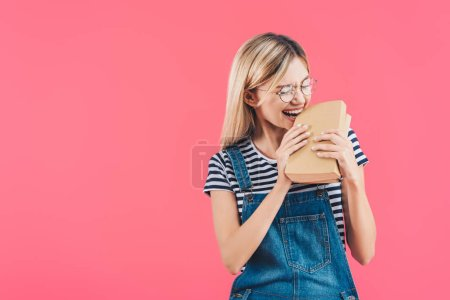 portrait of young student in eyeglasses biting books isolated on pink