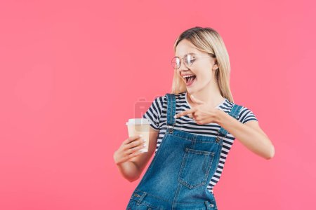 portrait of young woman pointing at coffee to go in hand isolated on pink