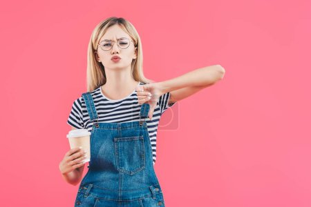 portrait of young woman with coffee to go showing thumb down isolated on pink
