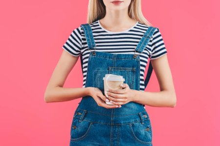 cropped shot of woman with coffee to go in hands isolated on pink