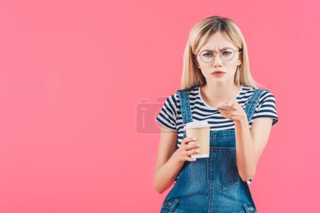 portrait of emotional woman with coffee to go pointing at camera isolated on pink