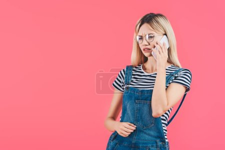 portrait of emotional woman in eyeglasses talking on smartphone isolated on pink