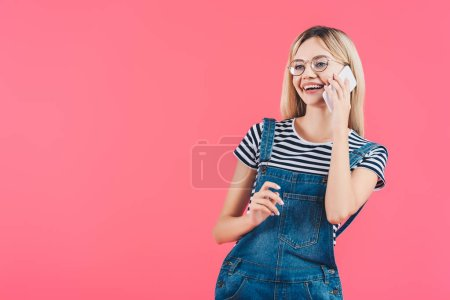 portrait of young smiling woman in eyeglasses talking on smartphone isolated on pink