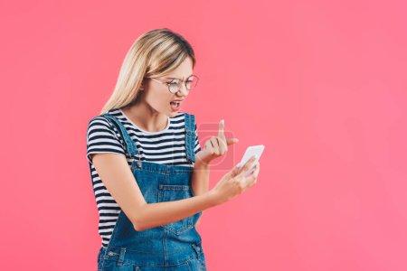 Portrait de jeune femme montrant majeur pour smartphone isolé sur rose
