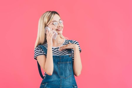portrait of young smiling woman talking on smartphone isolated on pink