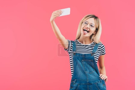 portrait of woman sticking tongue out while taking selfie on smartphone isolated on pink