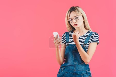 portrait of young woman showing fist to smartphone isolated on pink